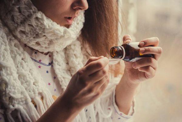 Женщина принимает микстуру от кашля