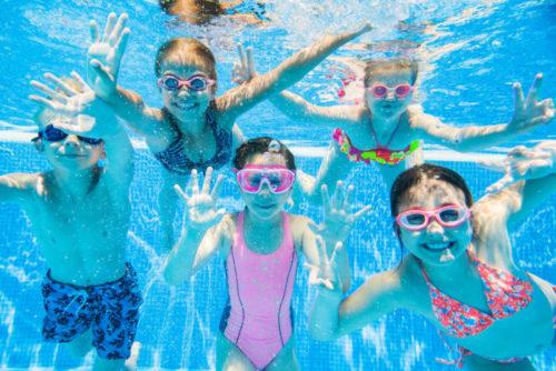 Дети плавают в бассейне под водой