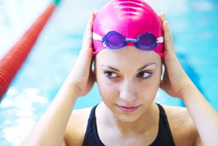 Пловец надевает шапочку для плавания