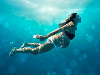 Беременная женщина плавает под водой