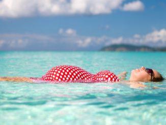 Беременная женщина плавает в море