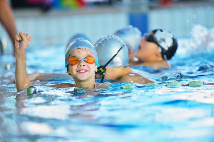 Ребенок на тренировке по плаванию в бассейне