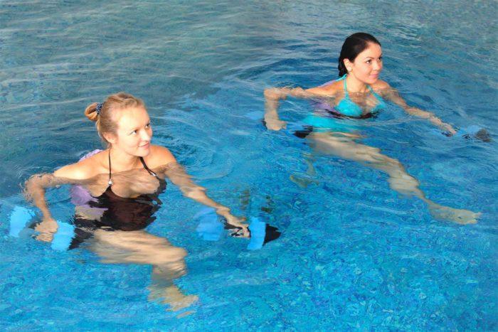 Женщины занимаются аквааэробикой с гантелями