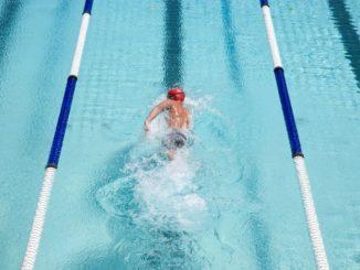 Мужчина плывет по дорожке в бассейне