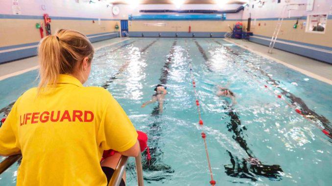 Спасатель в бассейне наблюдает за посетителями во время тренировки