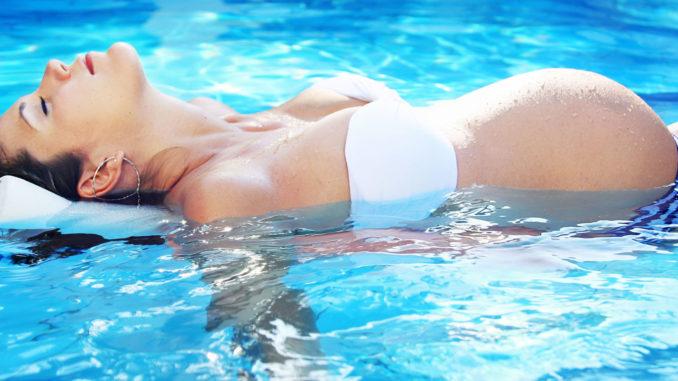 Беременная женщина лежит на воде
