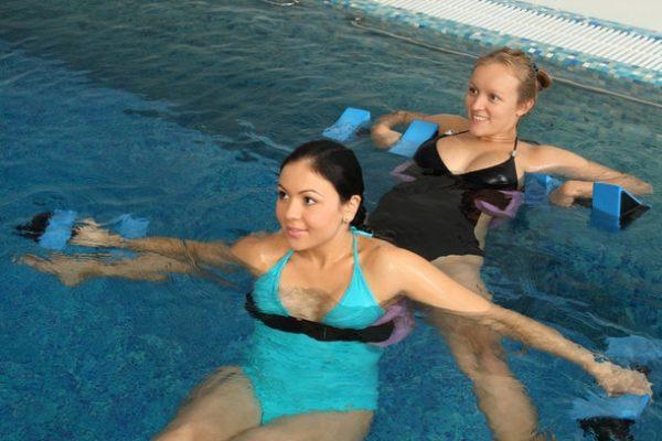 Беременные женщины выполняют упражнения с гантелями в воде